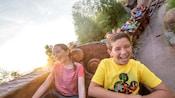 Un frère et une sœur sourient à bord du Seven Dwarfs Mine Train