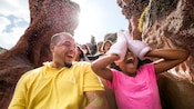 A smiling young girl wearing Mickey gloves covers her eyes as she rides Splash Mountain with her father