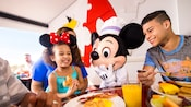 Mickey greets a young sister and brother enjoying breakfast at Chef Mickey's
