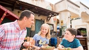 A father, young daughter and son sit down and enjoy street food for lunch outside the Harambe Market