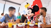 A young girl rubs noes with Minnie Mouse as her brother and father look on during a Character brunch