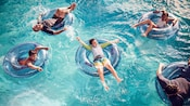 Five Guests float on inner tubes in a pool