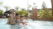 A father enjoys pool time with his two young boys