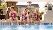 A group of four young girls wearing identical Disney themed bathing suits sit on a pool ledge and splash one another