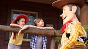 A little girl wearing a cowgirl hat and her young brother lean against a wooden rail and gaze up at Woody from Toy Story during their Character Meet and Greet