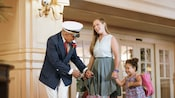 A mother and daughter are greeted by a Cast Member in the lobby of their Disney Resort hotel