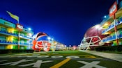 The illuminated football-themed courtyard at Disney's All-Star Sports Resort featuring gigantic helmets