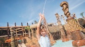 A little girls smiles with delight as she stands underneath a squirting fountain within the Lava Pool Kiki Tikis splash play area