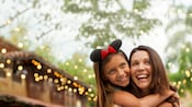 A daughter wearing Mickey ears hugs her mother