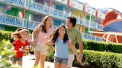 A smiling family of 4 including 2 daughters happily walk through the courtyard of Disney's All Star Sports Resort