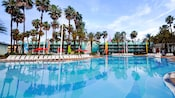 The pool area of Disney's All Star Resort with lounge chairs, umbrellas and surf board decor