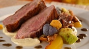 Slices of duck served with sauce, peaches, vegetables and more