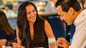 A woman dressed in upscale casual attire smiles at her husband as they enjoy a meal at Flying Fish