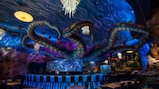 A giant octopus sits atop an aquarium where diners sit at a counter