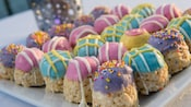 A plate of bonbon-shaped puffed rice treats topped with rainbow  frosting, sprinkles and glaze