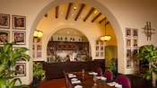 Spanish arches and movie-star portraits frame the bar area at The Hollywood Brown Derby dining room