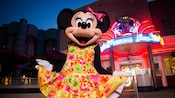 Minnie Mouse courtesies in a vibrant dress outside of Hollywood & Vine at Disney's Hollywood Studios