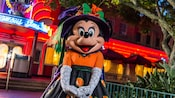 Minnie Mouse in Halloween dress stands outside of Hollywood and Vine restaurant at Disney's Hollywood Studios.