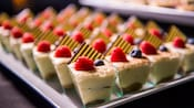 A tray of small cups containing a creamy dessert topped with 2 berries and a candy embellishment