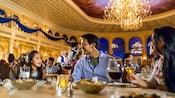 A young girl, her father and mother enjoy their meal at Be Our Guest restaurant