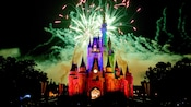 Cinderella Castle lit up in a multicolored glow beneath a sky of fireworks
