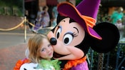 Minnie Mouse wearing a pointed cap and festive costume hugs a smiling young girl in a Tinker Bell costume