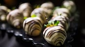 Several strawberries coated in white chocolate and streaked with dark chocolate are arranged in a triangle pattern on a platter