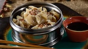Shu mai dumplings made of pork and shrimp wrapped in gyoza skin in a steamer basket with sauce