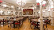 The Diamond Horseshoe dining room features white balustrade balconies and a self-playing piano
