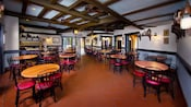 Dining area with tables, tiled floor and overhead fans at Tortuga Tavern