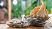 Traditional African breads and flatbreads in a wire basket, with a side dish of dips and condiments
