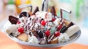 Un bol en forme d'évier de cuisine rempli de crème glacée, de biscuits, de bonbons, de gâteau, de crème fouettée et de fruits