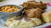 A 2-piece fried chicken dinner plated with a mashed potatoes & gravy, macaroni & cheese and cornbread