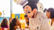 Chef Mickey greeting a delighted young girl at her table during an Easter Sunday dining experience