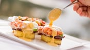 Yuzu hollandaise drizzles down from a spoon onto a plated serving of lobster benedict with 2 soft poached eggs, honey ham and marble potato hash