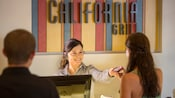 A hostess hands a beeper to a Guest at the check-in counter for California Grill