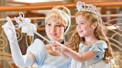 A girl dressed as Cinderella wields a wand with 2 hands as Cinderella herself looks on