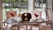 Round marble table with floral arrangement set for 2 with English tea service china and velvet gift bag