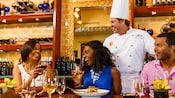 A mother with her daughter and son-in-law toasts a chef standing at their table