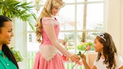 Princess Aurora passes out pink roses to Guests during My Disney Girl's Perfectly Princess Tea Party