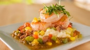 Three shrimp on a bed of creamy grits, green tomato chow-chow, green onions and chorizo and green garnish