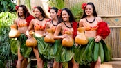 South Pacific dancers in grass skirts and holding gourds