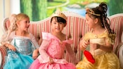 3 young girls sit on a couch wearing full princess regalia
