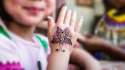 A child's hand with a glittery henna tattoo of a butterfly