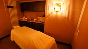 A massage table in a room with dimmed lighting
