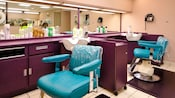 Turquoise salon chairs next to purple workstations in a beauty salon