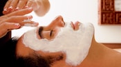 Um visitante recebe uma massagem facial no Mandara Spa no Walt Disney World Swan Hotel