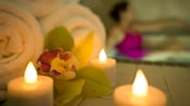 An orchid sits between 3 lit candles and rolled towels, close to a woman luxuriating in a spa