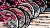 Close-up of a half dozen pink bikes stationed in bike stands