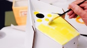 Close-up of a cardboard bird house being painted yellow